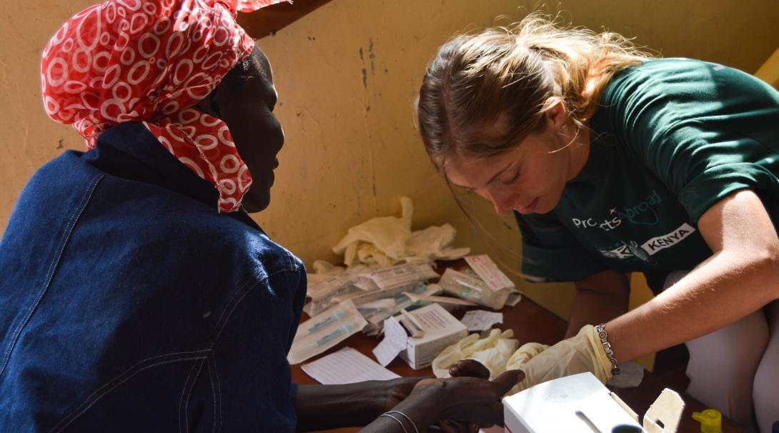 Female Medical intern treats a hand wound on a local woman during a Medical Outreach programme in Kenya.